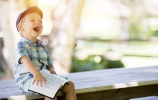Child enjoying reading a book while laughing and sitting on a dock