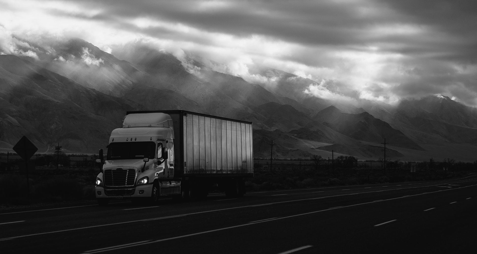 transport truck driving in black and white cost of claim