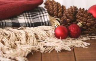 Holiday backdrop with pine cones, buffalo plaid blanket and red ornaments