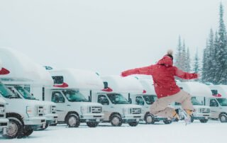 man jumping in the air on snowy rv parking lot