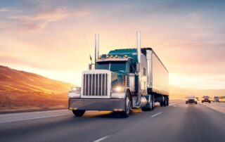 blue transport truck driving down the highway toward camera with sun setting behind contract