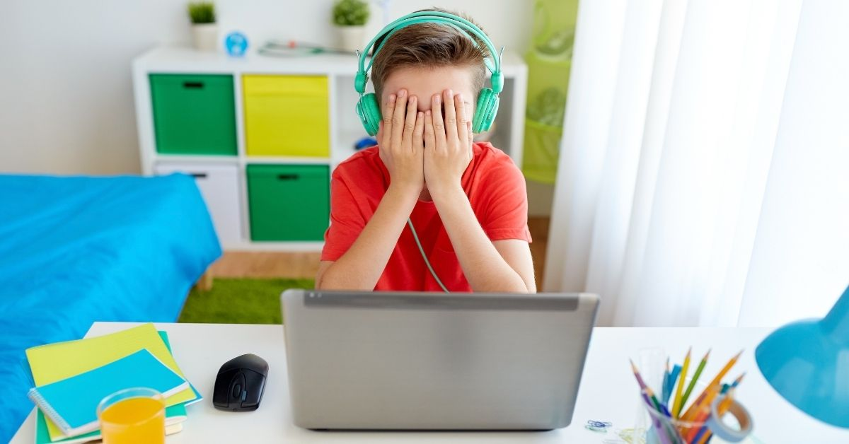 Kid sitting behind his computer with headphones on being cyber bullied in Ontario